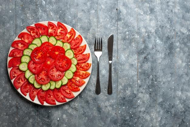Vue de dessus tomates rouges fraîches en tranches de salade fraîche sur le bureau gris