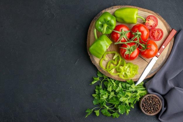 Vue de dessus des tomates rouges fraîches avec des verts et des poivrons verts sur une surface sombre