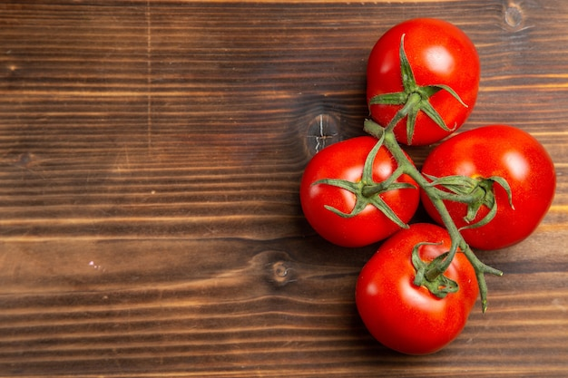 Vue de dessus tomates rouges légumes mûrs sur un bureau en bois brun