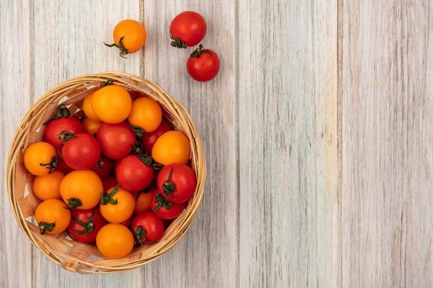 Vue de dessus des tomates rouges et orange arrondies sur un seau sur un mur en bois gris avec espace copie