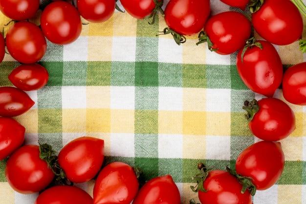 Vue de dessus des tomates sur tissu à carreaux avec espace copie