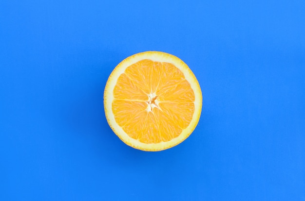 Vue de dessus d'une tranche de fruit orange sur fond clair de couleur bleue. une image de texture d'agrumes saturée