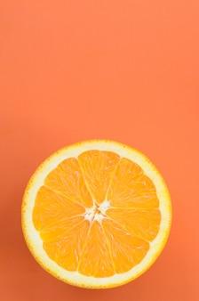Vue de dessus d'une tranche de fruit orange sur fond clair en couleur orange. une image de texture d'agrumes saturée