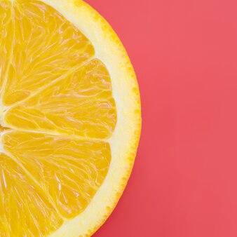 Vue de dessus d'une tranche de fruit orange sur fond clair de couleur rouge. une image de texture d'agrumes saturée