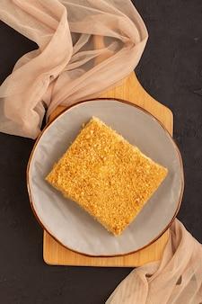 Une vue de dessus tranche de gâteau au miel délicieux à l'intérieur de la plaque sur la table en bois gâteau biscuit sucre sucré