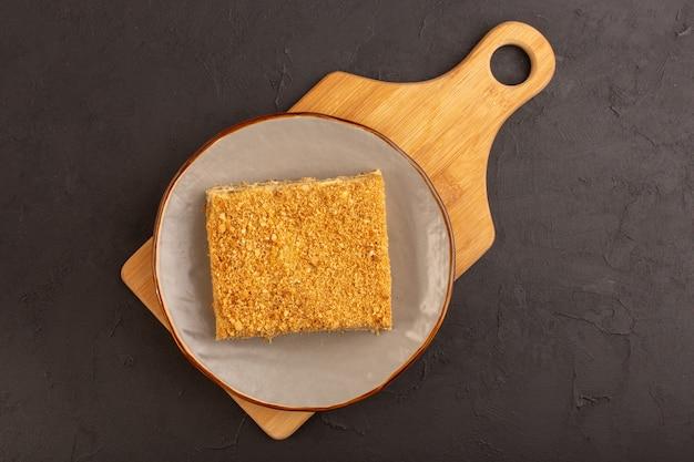 Une vue de dessus tranche de gâteau au miel délicieux et à l'intérieur de la plaque sur la table noire gâteau biscuit sucre sucré