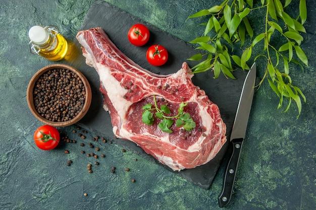 Vue de dessus tranche de viande fraîche avec tomates et poivre sur fond bleu foncé cuisine animal vache poulet nourriture couleur viande