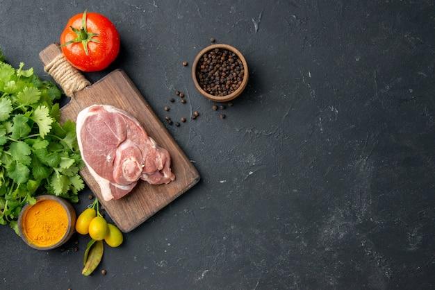 Vue de dessus tranche de viande fraîche viande crue avec des légumes verts sur un plat barbecue noir poivre cuisine nourriture vache nourriture salade repas animal