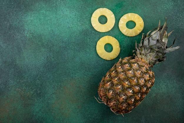 Vue de dessus des tranches d'ananas et d'ananas sur une surface verte