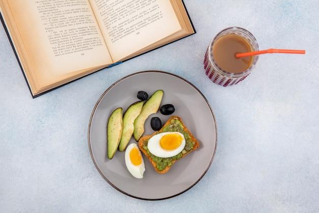 Vue de dessus des tranches d'avocat frais avec avocat sur tranche de pain avec œuf en sachet et olives noires sur plaque sur blanc