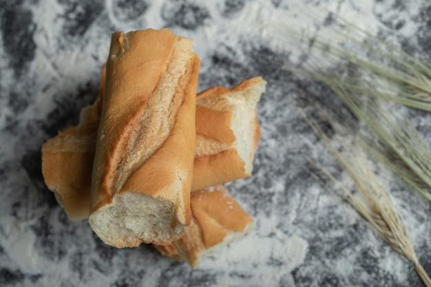 Vue de dessus des tranches de baguette fraîchement cuites sur fond blanc.