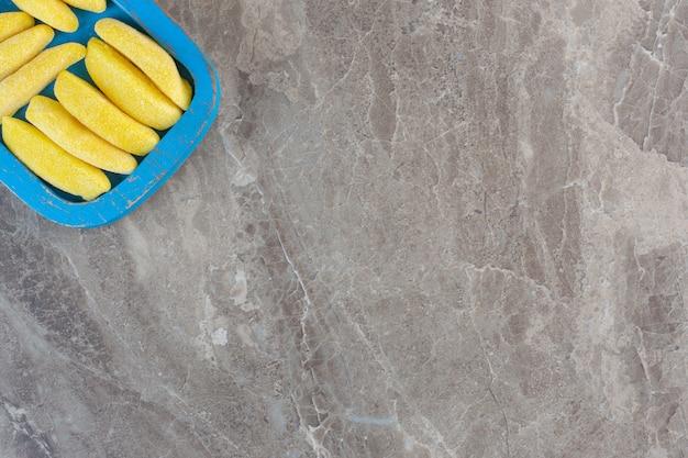 Vue de dessus des tranches de bonbons jaunes sur une planche de bois bleue sur fond gris.