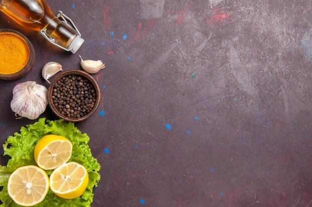 Vue de dessus des tranches de citron frais avec de l'ail et des assaisonnements sur noir