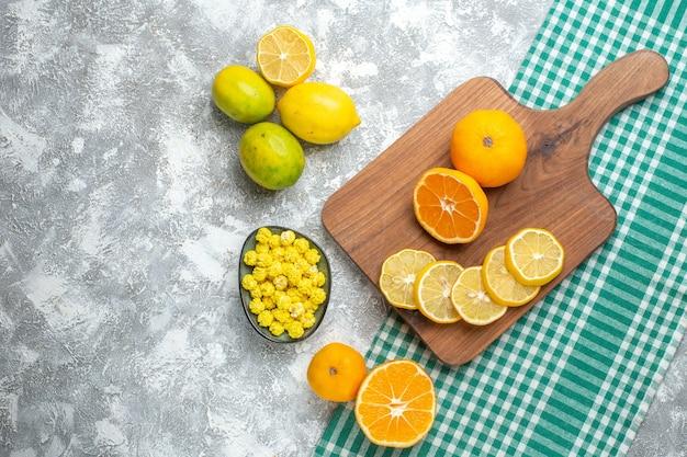 Vue de dessus des tranches de citron frais avec des bonbons sur une table lumineuse