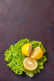 Vue de dessus des tranches de citron frais avec salade verte sur dark