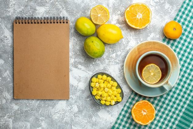 Vue de dessus des tranches de citron frais avec une tasse de thé sur une table lumineuse