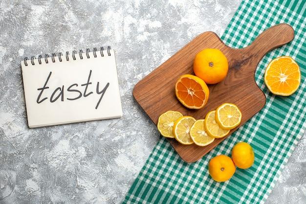 Vue de dessus des tranches de citron oranges sur des citrons de planche de bois sur une table à carreaux blanc vert