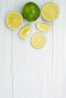 Vue de dessus en tranches de citron vert frais juteux et fruits aigres sur blanc