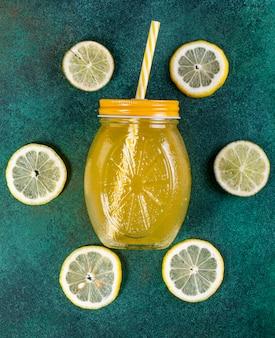Vue de dessus des tranches de citron vert avec des tranches de citron et du jus d'orange sur fond vert