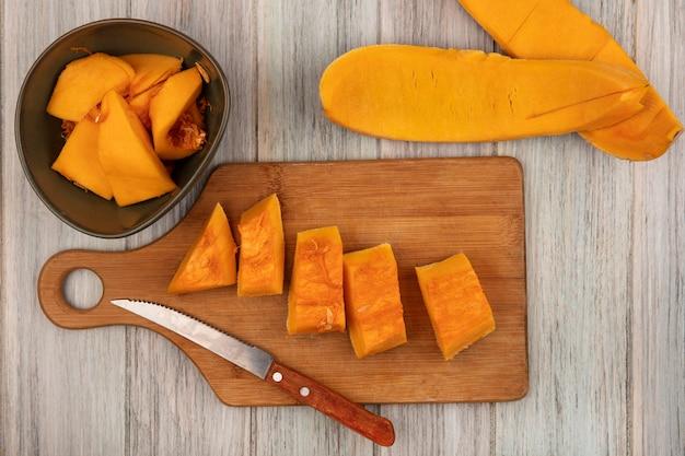 Vue de dessus de tranches de citrouille hachées fraîches sur une planche de cuisine en bois avec un couteau avec des pelures de citrouille isolé sur un fond en bois gris