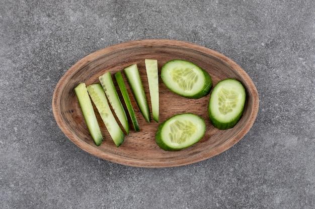 Vue de dessus des tranches de concombre tranchées et hachées sur une plaque en bois.