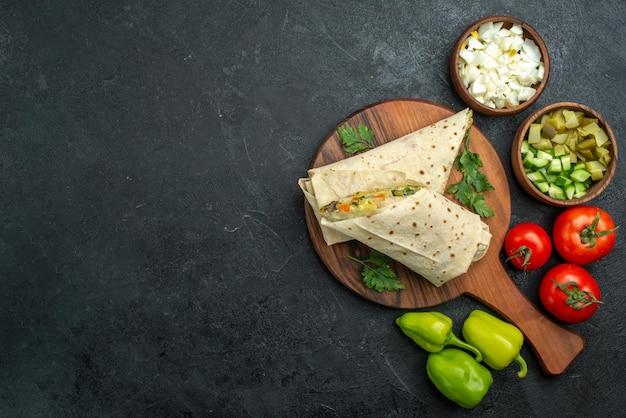 Vue de dessus en tranches de délicieux shaurma avec des légumes frais sur une surface grise burger salade sandwich repas repas