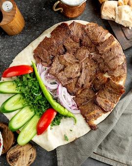 Vue de dessus des tranches de doner d'agneau placées sur du pain plat avec de la salade verte et des oignons