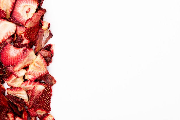 Vue de dessus des tranches de fraises séchées disposées sur fond blanc avec copie espace