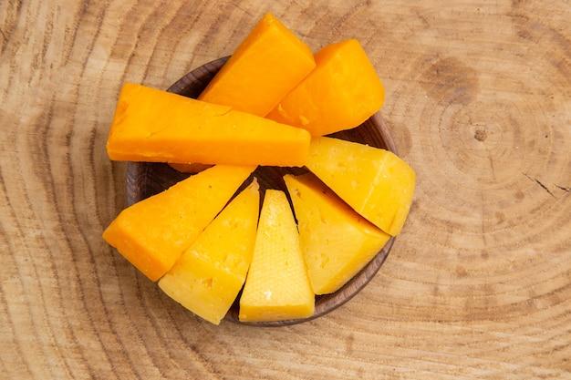 Vue de dessus des tranches de fromage dans un bol sur une table en bois