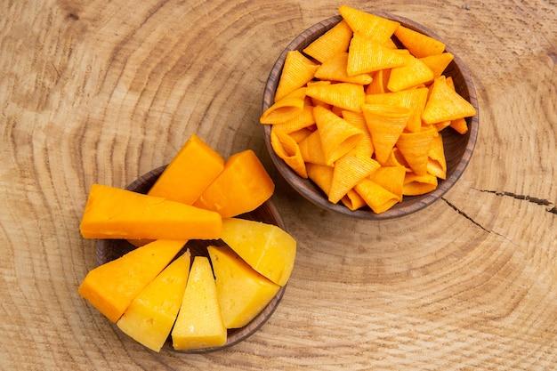 Vue de dessus des tranches de fromage et de frites dans des bols sur un sol en bois