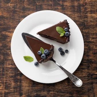Vue de dessus des tranches de gâteau au chocolat sur plaque avec spatule