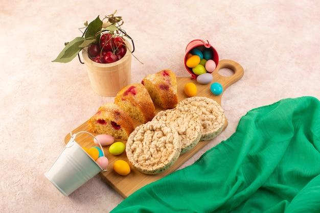 Une vue de dessus des tranches de gâteau aux cerises avec des bonbons et des biscuits sur le bureau rose gâteau biscuit sucre sucré