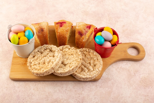 Une vue de dessus des tranches de gâteau aux cerises avec des bonbons et des biscuits sur le gâteau de bureau rose sucre sucré