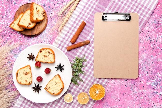 Vue de dessus des tranches de gâteau aux fraises et à la cannelle sur le gâteau de bureau rose cuire au four biscuit sucré couleur tarte biscuits au sucre