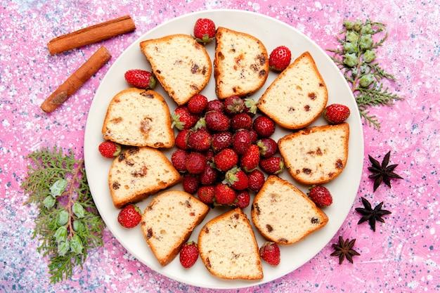 Vue de dessus des tranches de gâteau avec des fraises rouges fraîches sur le gâteau de bureau rose cuire au four biscuit sucré couleur tarte biscuit au sucre