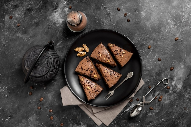 Vue de dessus des tranches de gâteau sur une plaque avec une théière et des grains de café