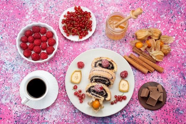 Vue de dessus des tranches de gâteau rouler avec différents fruits à l'intérieur de la plaque blanche avec du miel et de la cannelle sur le fond coloré gâteau biscuit couleur douce