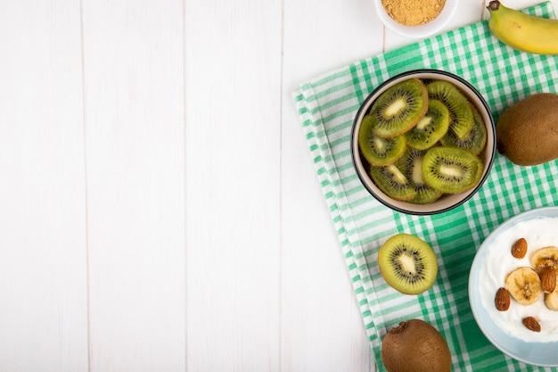 Vue de dessus des tranches de kiwi dans un bol et du yaourt à la banane sur une serviette de table à carreaux sur blanc avec copie espace