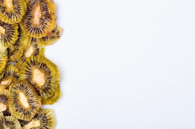 Vue de dessus des tranches de kiwi séchées sur fond blanc avec copie espace