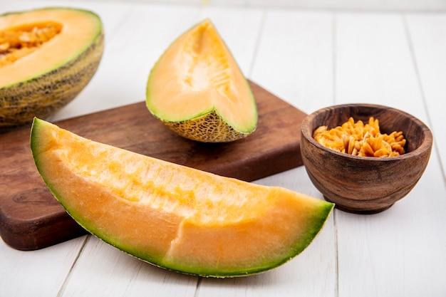 Vue de dessus des tranches de melon cantaloup frais sur planche de cuisine en bois sur bois blanc