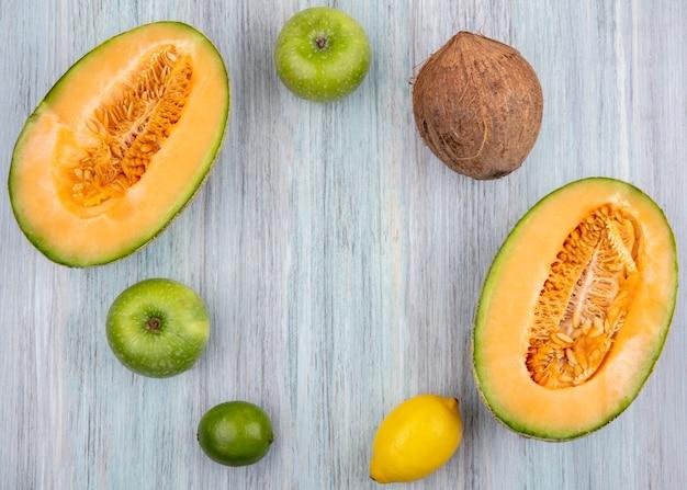 Vue de dessus des tranches de melon cantaloup frais avec des pommes vertes de noix de coco et des citrons sur fond gris avec espace copie