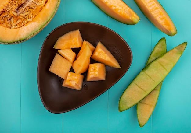 Vue de dessus des tranches de melon cantaloup sucré mûr sur un bol brun sur une surface bleue