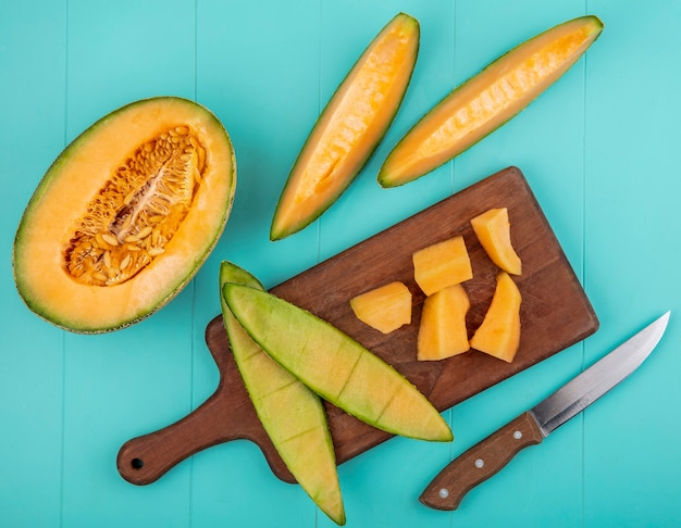 Vue de dessus des tranches de melon cantaloup sucré mûr sur une planche de cuisine en bois sur une surface bleue