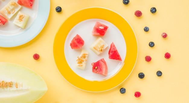 Une vue de dessus de tranches de melon et melon d'eau sur une plaque avec des myrtilles et framboises