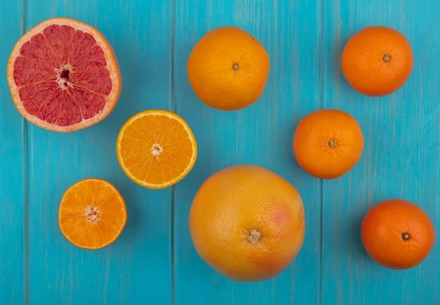 Vue de dessus avec tranches et orange et pamplemousse entier sur fond turquoise