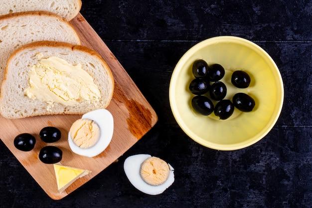 Vue de dessus des tranches de pain et de beurre à bord avec des olives et des œufs durs sur fond noir
