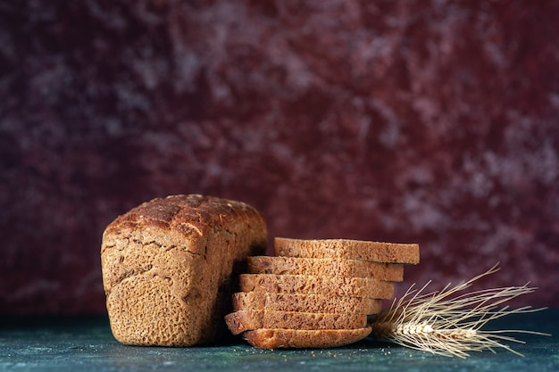 Vue de dessus des tranches de pain noir diététique sur fond de couleurs mélangées bleu marron avec espace libre