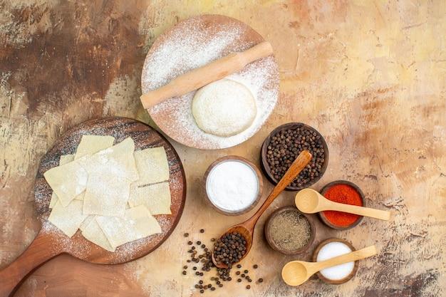 Vue de dessus des tranches de pâte crue avec des assaisonnements sur le bureau de la crème