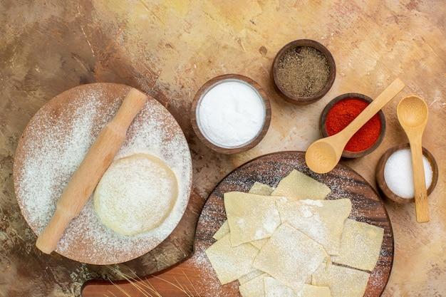 Vue de dessus des tranches de pâte crue avec de la farine et des assaisonnements sur le bureau de la crème