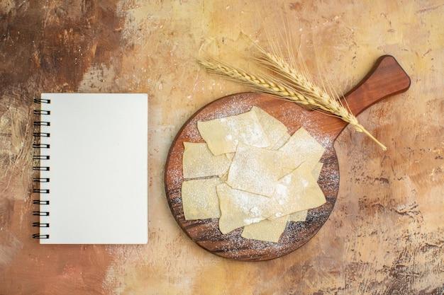 Vue de dessus des tranches de pâte crue avec de la farine sur un bureau en bois
